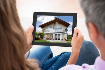 Couple Looking At House Photo On Digital Tablet