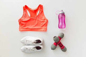 close up of sportswear, dumbbells and bottle