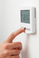 Close Up Of hand Adjusting Digital Central Heating Thermostat