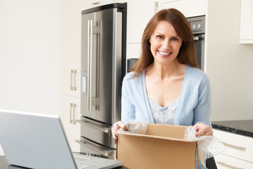 Woman Unpacking Online Purchase At Home