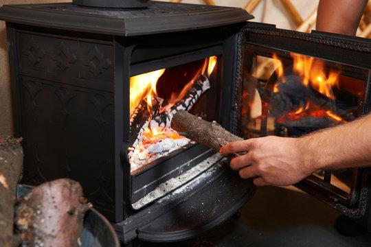 Man Putting Log Onto Wood Burning Stove