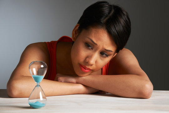 Sad Young Woman Looking At Hourglass