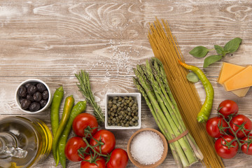 Fresh organic pasta, asparagus, tomatoes, peppers, olives, capers, olive oil, parmesan cheese  ingredients on wood surface