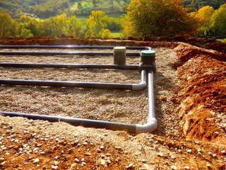 The top layer of pipework, after the membrane, sand and gravel had been applied, during the construction of a sand and gravel drainage system