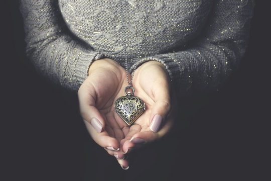 Heart necklace in woman hands.
