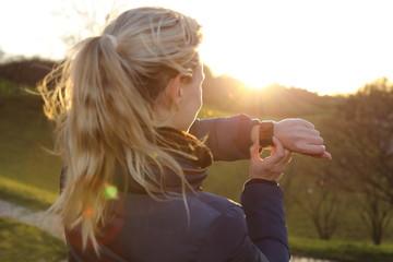Frau mit Smartwatch bei Gegenlicht im Park
