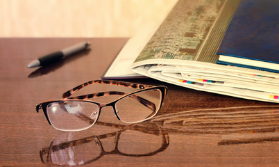 Glasses and Newspapers on the table surface.