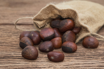 roasted chestnuts in canvas bag on wooden background