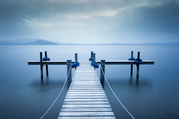 Lake Zug. Wooden pier on the lake. Fog. Long exposure.
