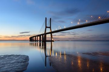 Ponte Vasco da Gama ao anoitecer com iluminação.