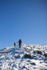 Mountaineers climb the snowy slope.
