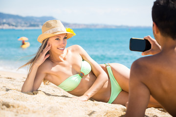 Man taking photo of woman on beach