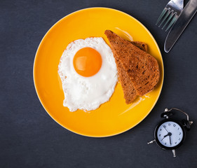 Fried egg and bread on the plate and alarm clock on the black ba