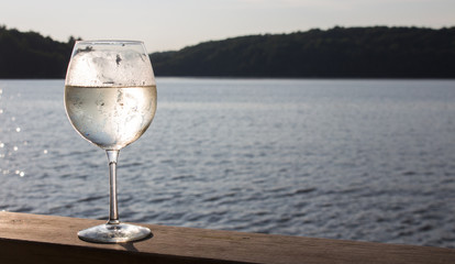 White wine spritzer on the wooden deck of a Canadian cottage sunset landscape