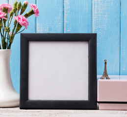 Blank frame, pink flower and souvenir Eiffel tower.