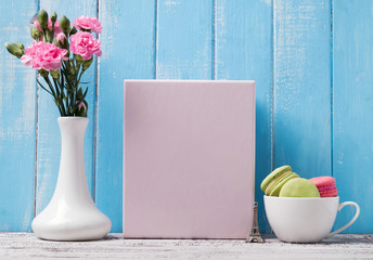 Blank poster, flowers and macarons in the cup
