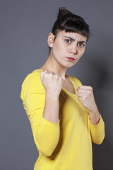female fighting concept - unhappy 20s woman showing her fists in the foreground for self-defense or rebellion,studio shot