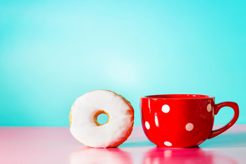 White donut with big red mug on pastel blue and pink background