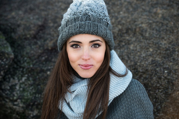 Beautiful smiling woman wearing winter warm clothes and hat