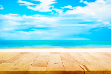 Wood table top on blur white sand beach and blue sky background
