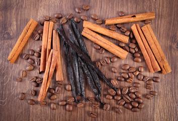 Fragrant vanilla, cinnamon sticks and coffee grains on wooden surface