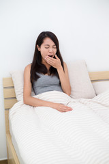 Woman yawning in bed, after waking up
