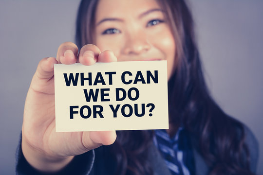 WHAT CAN WE DO FOR YOU? message on the card shown by a businesswoman