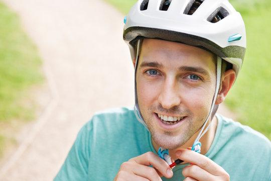 Man Fastening Strap Of Cycling Helmet