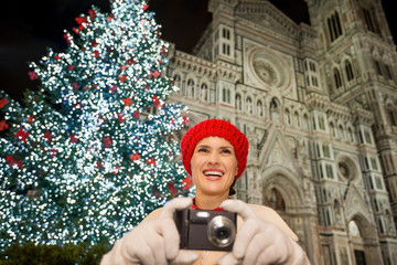 Young woman taking photos near Christmas tree in Florence, Italy