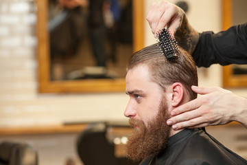 Attractive young bearded hipster attending the hairdresser