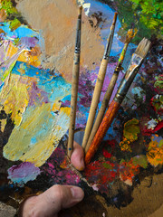 Painter holding a palette for mixing oil paints. The color palette close up.