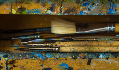 Artist paintbrushes closeup on old wooden easel