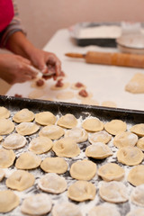 Just made dumpling meat on a pan in focus and womans hands working it on background
