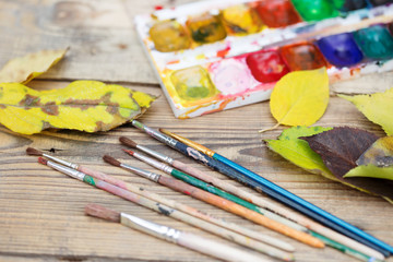 Plastic paint palette with paint, brushes and yellow leaves on w