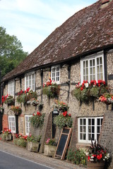 Quaint Old British Pub Decorated with Window Boxes and Hanging Baskets of Flowers in Summer.