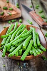 pods of fresh organic green beans in a wooden bowl closeup