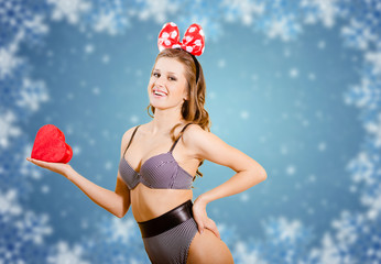 Picture of young attractive female in swimsuit holding red heart over winter snowflakes abstract background