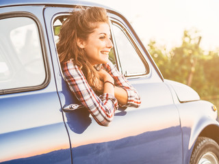 A smiling young and beautiful woman looking out the window of a car, smiling and looking away. After a drive through the hills of Tuscany with her boyfriend stop to admire the sunset