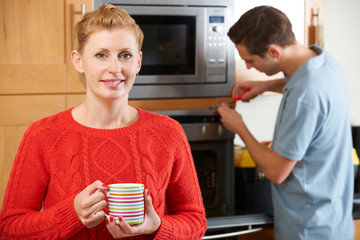 Woman Smiling As Cooker Is Repaired