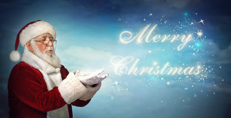 Santa Claus blowing Merry Christmas from snow