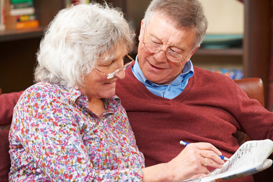 Senior Couple Doing Crossword Puzzle In Newspaper Together