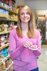 Woman Looking At Shopping List On Mobile Phone In Supermarket