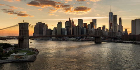 Fotomurales - Lower Manhattan and Financial District skyline at sunset with the Brooklyn Bridge over the East River. Silhouettes of skyscrapers catch the last last of the daylight. New York City