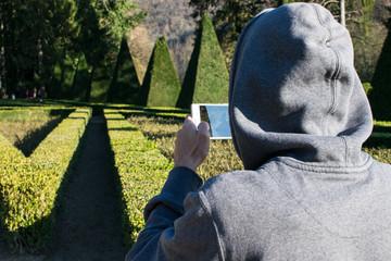 Un homme prend une en photo avec son téléphone portable dans le parc du château de Vizille 2
