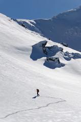 mountaineer climbing a steep face during winter