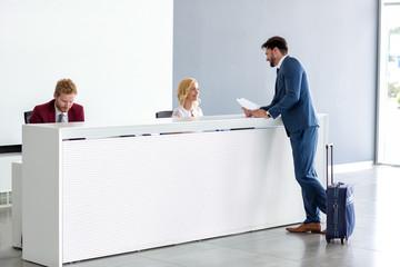 Businessman flirting at reception with female receptionist