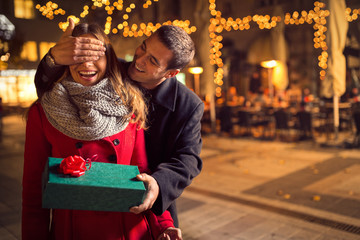 Man  keeps his girlfriend eyes covered while  she giving a gift