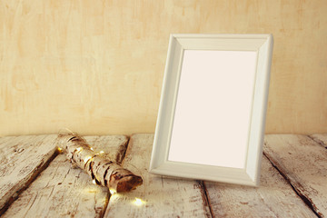 image of old tree log with fairy christmas lights and blank photo frame on wooden table.selective focus. template ready to put photography