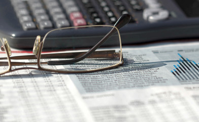 Financial accounting concept. Reading glasses and calculator on financial newspaper stock charts. Image of the objects typical for business environment
