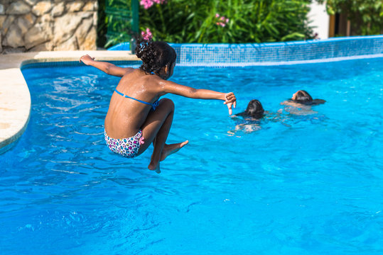 Brazilian girl jumping in tropical blue swimming pool in summer